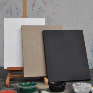 Différents châssis entoilés dans un atelier avec de la peinture et un chevalet.