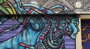Un personnage de profil, courant, peint sur une façade de Street Art City